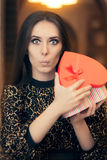 Surprised Beautiful Woman Opening Heart Shape Gift. Portrait of a funny girl with present box in a restaurant Stock Photography