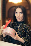 Surprised Beautiful Woman Opening Heart Shape Gift. Portrait of a funny girl with present box in a restaurant Stock Photos