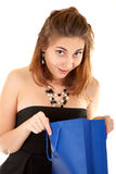 Surprised beautiful woman with paper bag. Surprised beautiful woman in black dress with blue paper bag try to discover what is inside the bag Stock Photography