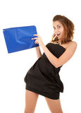 Surprised beautiful woman with paper bag. Surprised beautiful woman in short black dress with blue paper bag try to discover what is inside the bag Stock Photo