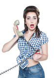 Surprised beautiful woman in pin-up style with retro telephone. Over white Stock Photography