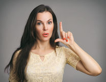 Surprised Beautiful Woman pointing up her finger. Over gray background Royalty Free Stock Images