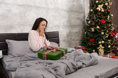 Surprised beautiful woman wake up and rejoice at her christmas p Stock Photo