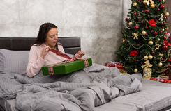 Surprised beautiful woman wake up and unpacking her christmas pr. Esent while sitting in a bed in the bedroom in loft style with Christmas tree with a lot of Royalty Free Stock Image