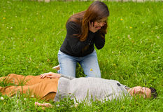 Surprised beautiful woman watching a handsome young man that is over a grass, cardiopulmonary resuscitation concept, in Royalty Free Stock Photos