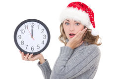 Surprised beautiful woman in winter clothes and santa hat holdin. G clock isolated on white background Royalty Free Stock Photo