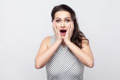 Surprised beautiful young brunette woman with makeup and striped dress standing touching her face and looking at camera with royalty free stock photos