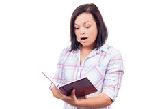 Surprised Beautiful Young Woman Reading a Book Stock Images