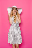 Surprised Beautiful Young Woman In Summer Dress And Sun Hat Is Holding Hand On Chin. Beautiful young woman in white dotted summer dress and sun hat is holding Royalty Free Stock Photography