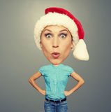 Surprised bighead girl in santa hat. Over grey background Stock Photos