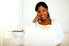 Surprised black woman eating fresh vegetable salad. Portrait of a surprised adult woman eating fresh vegetable salad while is sitting in front of her laptop Royalty Free Stock Photo