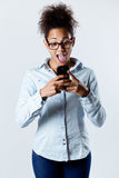 Surprised black woman looking the mobile Stock Photos