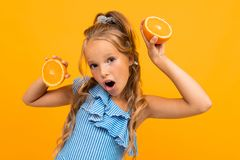 Surprised Blond Attractive Girl With Oranges On A Yellow Background Royalty Free Stock Photo