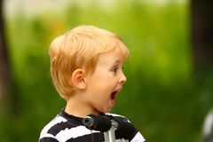 Surprised blond boy with mouth open. Surprised blond boy (green background Royalty Free Stock Photography