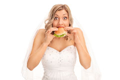 Surprised blond bride eating a sandwich Stock Photography