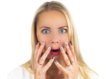 Surprised blond girl with blue eyes screams and closes mouth with her hands from surprise. Presenting your product. Isolated. On white background. Expressive Stock Image