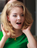 Surprised blond girl client by hairdresser in hair beauty salon Royalty Free Stock Photography
