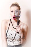 Surprised blond pinup pretty woman in polka dot dress looking through spatula on white background portrait Stock Photos