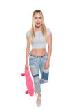 Surprised blonde girl holding skateboard and looking at camera isolated on white Royalty Free Stock Photo