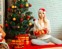 Surprised blonde girl in santa hat with a lot of christmas gifts Royalty Free Stock Image