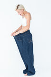 Surprised blonde wearing too large pants Stock Image