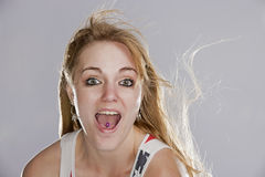 Surprised Blonde woman. A beautiful young blonde woman with an excited surprised expression on her face as she smiles with her eyes and the wind blows her golden Royalty Free Stock Image