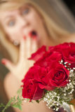 Surprised Blonde Woman Accepts Gift of Red Roses Stock Photos