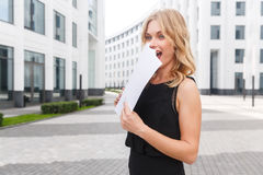 Surprised blonde woman holding documents. Live facial expressions. Outdoors portrait of surprised blonde woman holding documents. Live facial expressions Royalty Free Stock Photography