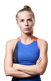 Surprised Blue eyed blond girl. With tail hair in sportswear with crossed arms and front standing on white isolated background Royalty Free Stock Photos