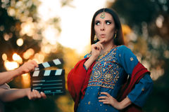 Surprised Bollywood Actress Wearing an Indian Outfit and Jewelry. Professional cinema star shooting a scene Royalty Free Stock Images