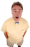 Surprised bowtie man. A surprised man looking upward, wearing a yellow shirt and a tiny blue bowtie Royalty Free Stock Image