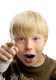 Surprised boy. Cute amazed blond boy, pointing with his finger, isolated on white background Stock Images