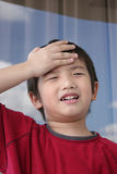 Surprised boy. A surprised boy wearing red tee holding his forehead Stock Image
