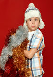 Surprised boy child portrait in santa hat on red, having fun and emotions, winter holiday concept Stock Image