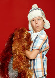 Surprised boy child portrait in santa hat on red, having fun and emotions, winter holiday concept Royalty Free Stock Image