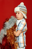 Surprised boy child portrait in santa hat on red, having fun and emotions, winter holiday concept Royalty Free Stock Photo