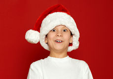 Surprised boy child portrait in santa hat on red, having fun and emotions, winter holiday concept Royalty Free Stock Photography