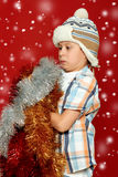 Surprised boy child portrait in santa hat on red, having fun and emotions, winter holiday concept Stock Photos