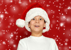 Surprised boy child portrait in santa hat on red, having fun and emotions, winter holiday concept Stock Photography