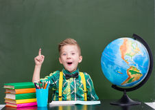 Surprised boy in classroom showing finger up.  Royalty Free Stock Photography