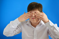 Surprised boy closes  eyes with hands Stock Images