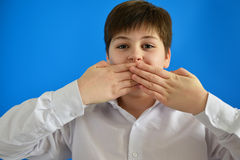 Surprised boy closes  mouth with hands Royalty Free Stock Photo