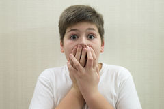 Surprised boy closes the mouth with  hands. Surprised boy closes the mouth with his hands Stock Images