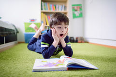 Surprised boy is discovering something from the book Royalty Free Stock Photos