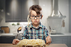 Surprised boy in glasses with spaghetti. Surprised young boy in glasses with spaghetti Stock Photo