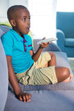 Surprised boy holding remote control while sitting on sofa at home Royalty Free Stock Photo