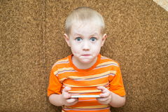 Surprised boy holding a smartphone in the hands Stock Photography