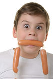 Surprised Boy Holds Sausage In Mouth Stock Photo