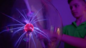 Surprised boy lights the lamp without electricity. Boy conducts electricity and lights the lamp using his body and plasma globe. Tesla globe with electric stock video footage