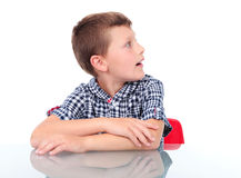 Surprised boy looking at left. Surprised boy sitting near table and looking at left Royalty Free Stock Image